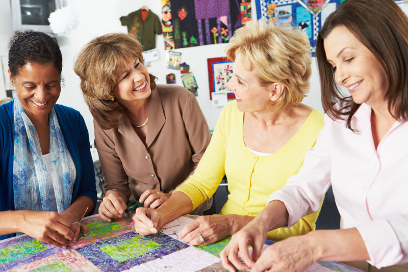 Gruppe von Frauen nähen Patchworkdecke