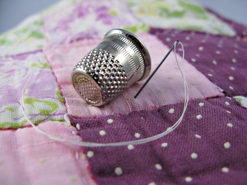 Patchworkdecke mit Nadel und Fingerhut